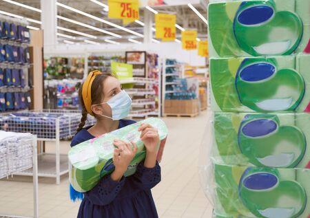 Girl in medical mask shopping in supermarket