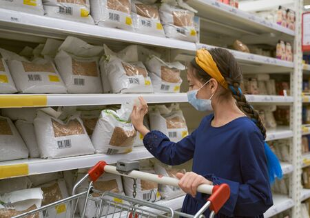 Girl makes stock of products. Reaching food shelf Standard-Bild