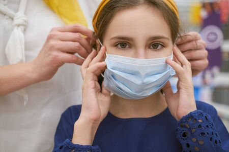 Mother helps her daughter put on protective mask
