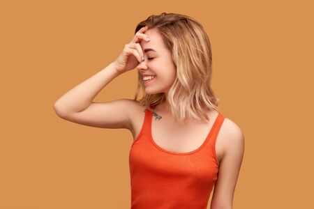Girl laughs loudly clutches forehead, closes eyes Standard-Bild