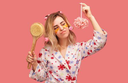 girl wears hair curler, sponges on face under eyes