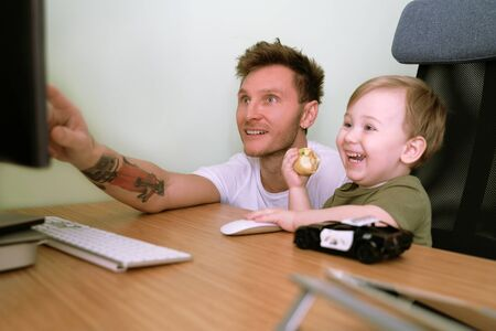 Small child is busily using computer, using mouse