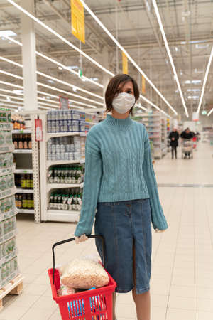 Girl in disposable medical mask shopping in supermarket during an outbreak of coronavirus pneumonia, makes panic stock of products. Empty store shelves, set of products for quarantine self-isolation