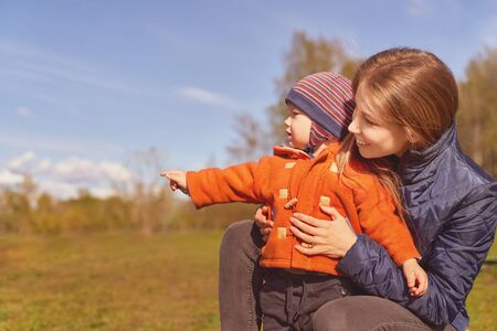 Young mother with long, well-groomed ginger hair wears blue warm jacket, young son in sweaters cap for year or two. child points with his index finger at free space for inserting text advertising Standard-Bild