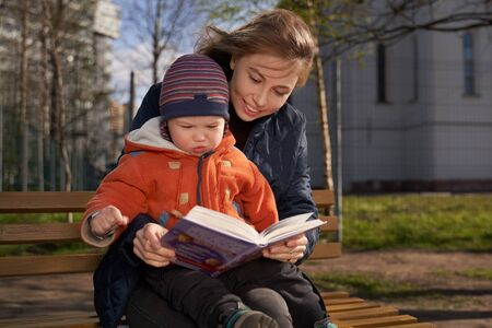 A girl hugs a child, sitting on a bench, child on womans lap, reading book, telling story Standard-Bild
