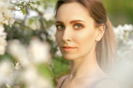 A young smiling girl with green eyes stands in a blooming Apple tree in the spring and sniffs the flowers on a pleasant Sunny day. Close up portrait of a beautiful woman in the Park