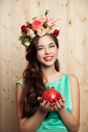 Smiling girl with flower crown and pomegranate photo