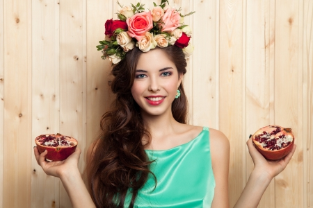 Smiling girl with flower crown and pomegranate Фото со стока