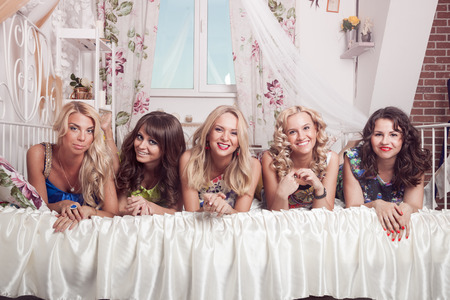 hen party: Group of cheerful beautiful woman lying on bed. Bachelorette. Stock Photo