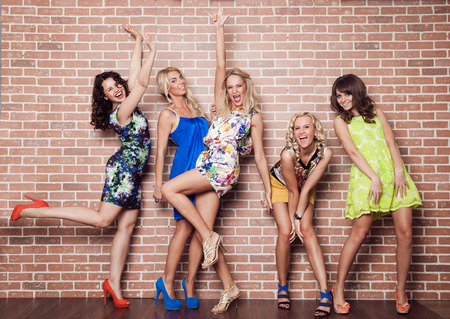 to dress: Group of cheerful beautiful woman on brick background. Bachelorette.
