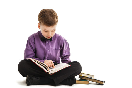 Young boy reads a book isolated