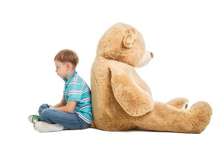 young boy sitting sad with a big teddy bear
