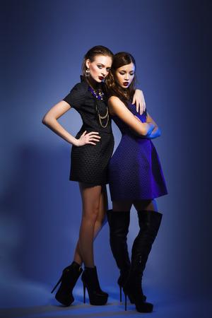 dos modelos de moda posando en fondo azul