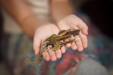 Little girl holding batch of old keys. Close up photo.