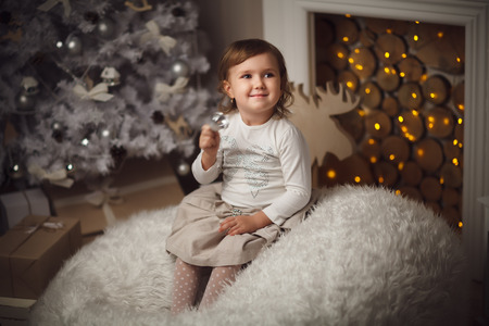 baby open present: little cute girl sitting near christmas tree and fireplace. Cozy interior Stock Photo