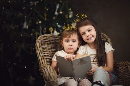 baby open present: Two little cute girls sitting near christmas tree and reading book. Cozy interior