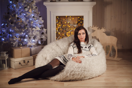 young tree: Attractive young woman lies near christmas tree. Home interior.