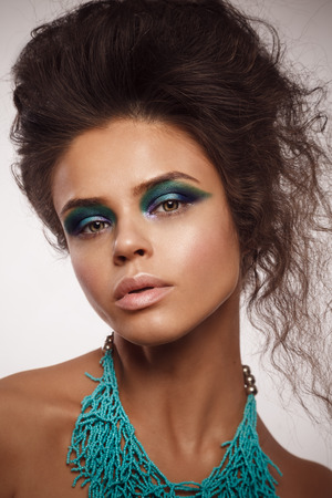 lips glow: Beauty studio portrait of  sun-tanned woman with bright blue and green make-up.