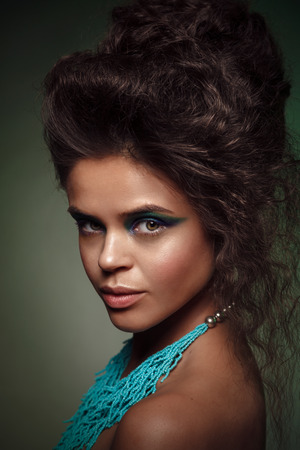 face to face: Beauty studio portrait of  sun-tanned woman with bright blue and green make-up.