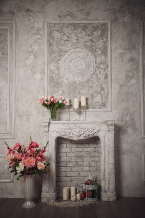 pilasters: Interior with grey fretwork background, fireplace and flowers.