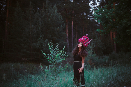 amaranthine: Beautiful woman in forest with crown from purple peonies.