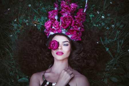 magenta dress: Beautiful woman with crown from purple peonies. Stock Photo