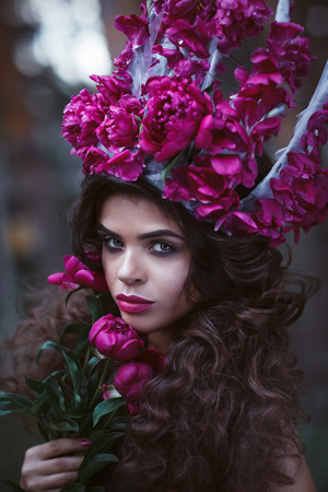 magenta dress: Beautiful woman with crown holding purple peonies.