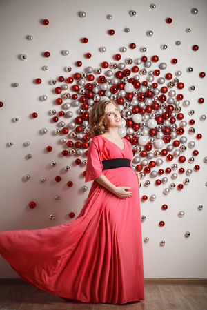 Young beautiful pregnant woman in coral dress on christmas background Stock Photo