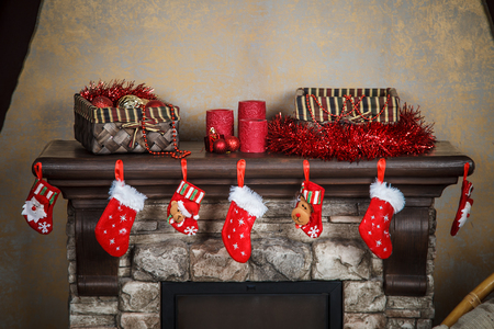 stuffer: Christmas red stocking hanging from a mantel or fireplace, decorated for Stock Photo