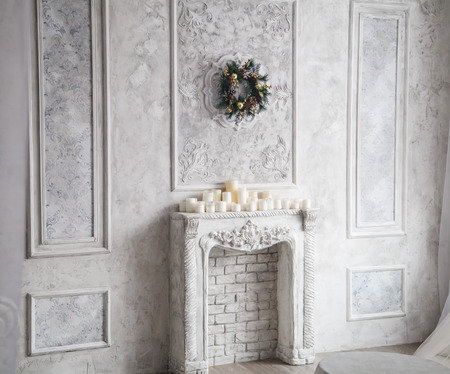 grecas: Interior with grey fretwork background, fireplace and christmas wreath