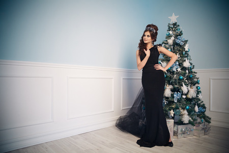 corona navidad: Gorgeous young woman in black dress with perfect makeup and hairstyle in blue christmas interior.