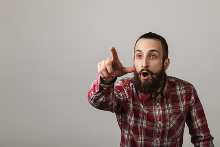 Bearded handsome man surprised in red squared shirt on grey background.
