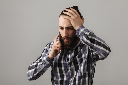 Bearded handsome sad man is talking by phone in blue squared shirt on grey background. Stock Photo