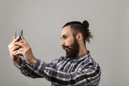 narcissist: Bearded handsome man is taking selfie by phone in blue squared shirt on grey background.