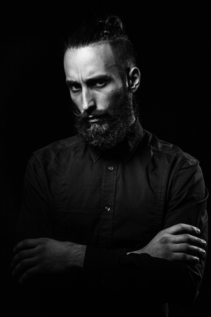 narcissist: Black and white studio portrait of a handsome man with a beard in the black shirt.