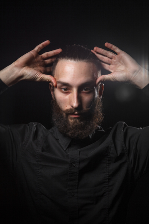 narcissist: Studio portrait of a handsome man with a beard in the black shirt Stock Photo