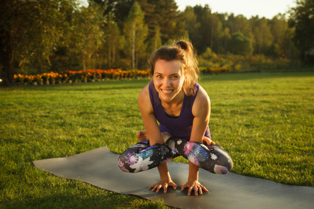 Young attractive girl practicing yoga outdoor. Summer sunset 스톡 콘텐츠