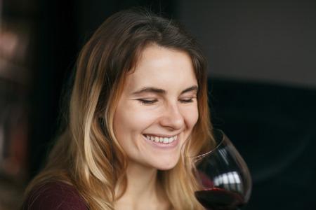De aantrekkelijke vrouw drinkt rode wijn in het restaurant.