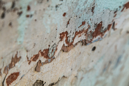 Macro photography of layered peeling plaster with remains of olad paint. Stock Photo