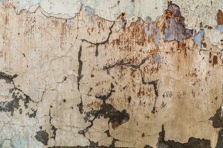 Old dirty concrete wall with peeling old paint and cracks. Stock Photo