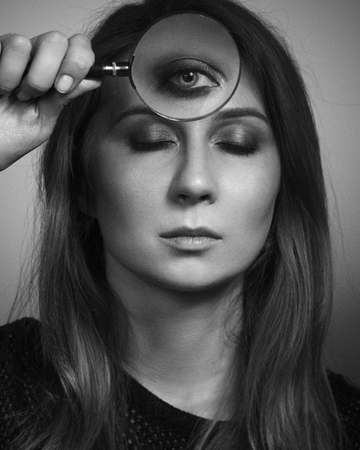 Woman see by third eye through magnifier glass. Black and white photo