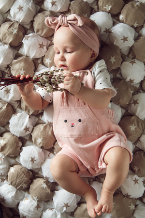 Portrait of cute baby girl wearing pink clothes holding willow. Stok Fotoğraf