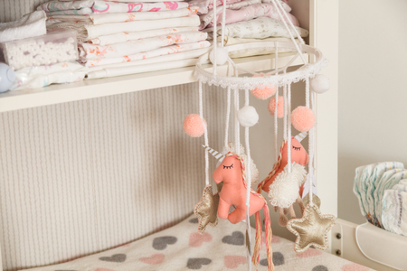 Hanging toys on the baby changing table.