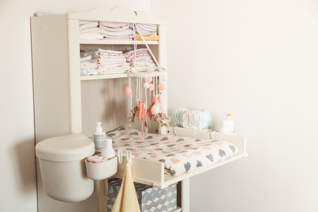 Baby changing table in light bedroom.