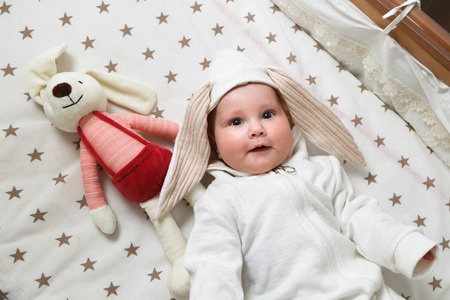 Cute baby in the rabbit costume lying in the bed with toy