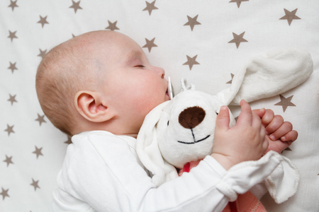 baby is sleeping in the bed with rabbit toy