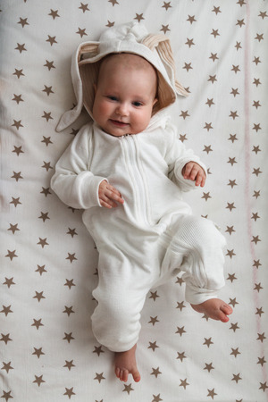 Cute baby in the rabbit costume lying in the bed