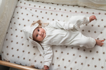 Cute baby in the rabbit costume lying in the bed Reklamní fotografie