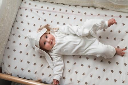 Süßes Baby im Hasenkostüm im Bett liegend Standard-Bild