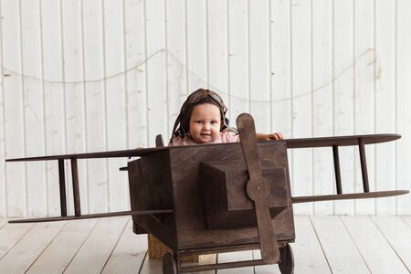 Cute baby pilot in the helmet sitting in the wooden airplane